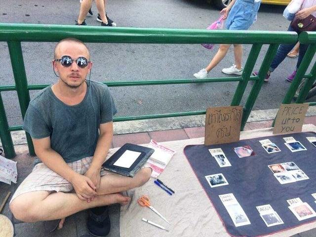 Ein junger Mann mit Sonnenbrille sitzt im Schneidersitz auf dem Boden. Neben ihm liegen Postkarten.