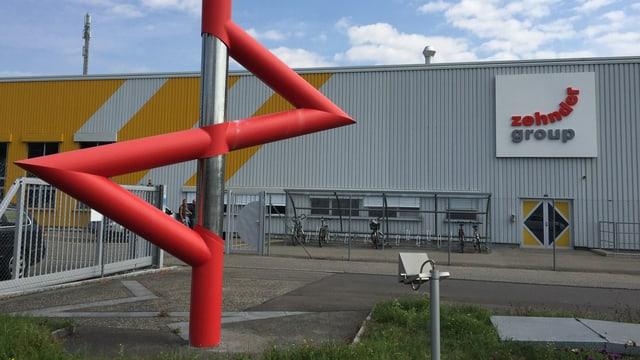 Fabrikgebäude, davor Kunstwerk