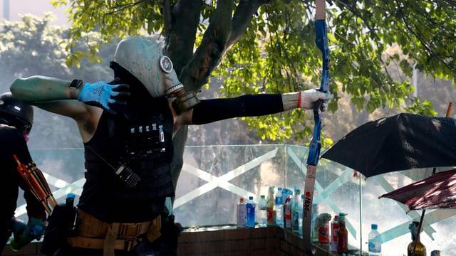 Ein regierungsfeindlicher Demonstrant benutzt einen Bogen bei Zusammenstössen mit der Polizei