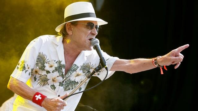 Polo Hofer singend auf der Bühne mit dem Mikrofonständer in der Hand.