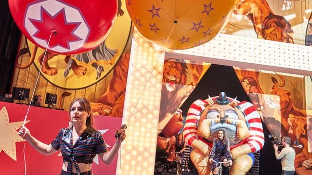 Ein buntes Bühnenbild mit Bildern von Löwen und pompösen Ballonen.