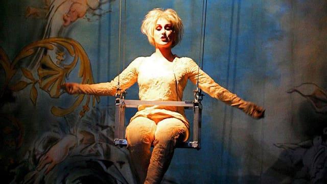 Bühnenbild: Eine weiss geschminkte Frau sitzt singend in einer Schaukel.