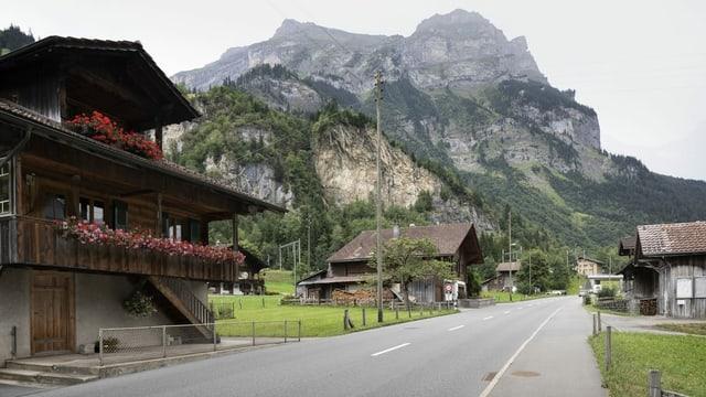 Ein Dorf, dahinter eine Felswand.