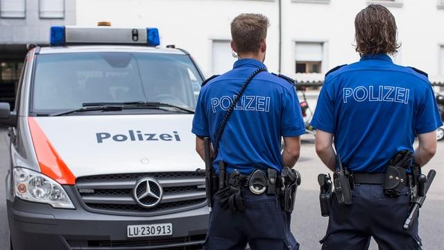 Ein Polizeiauto, davor stehen zwei Polizisten.