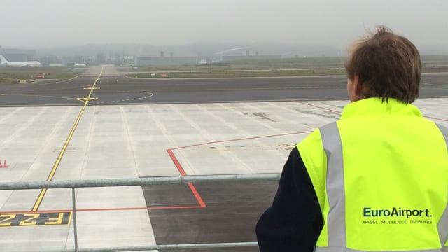 Man sieht eine Person auf der Terrasse auf dem EuroAirport, die auf das Rollfeld schaut.