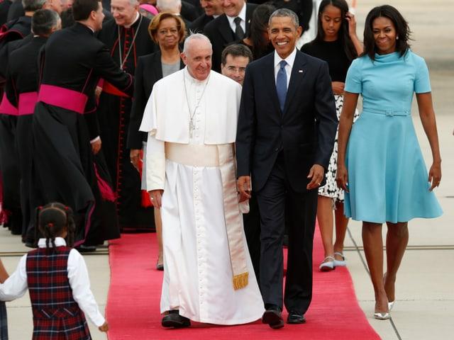 Barack Obama und der Papst schreiten über einen roten Teppich.