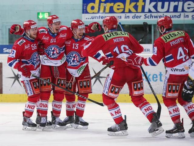 Fünf Spieler umarmen sich auf dem Eis.