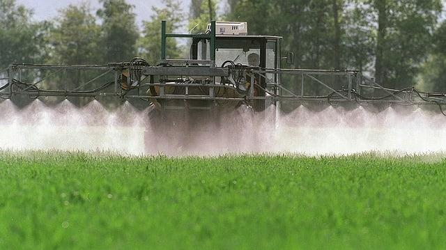 Traktor mit Sprühvorrichtung besprüht Feld mit Pflanzenschutzmitteln