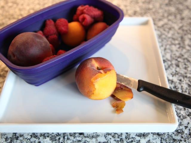 Pfirsich wird mit einem Messer in kleine Stücke geschnitten.