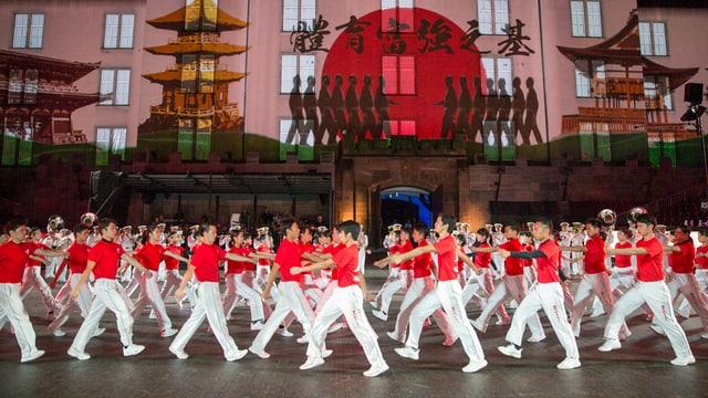 Japanerinnen und Japaner in weissen Trainingshosen und roten T-Shirts, dahinter die Fassade der Kaserne mit japanischen Motiven.