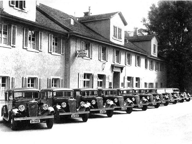 Zehn alte Taxis stehen vor einem langen Haus. Schwarz-weiss.