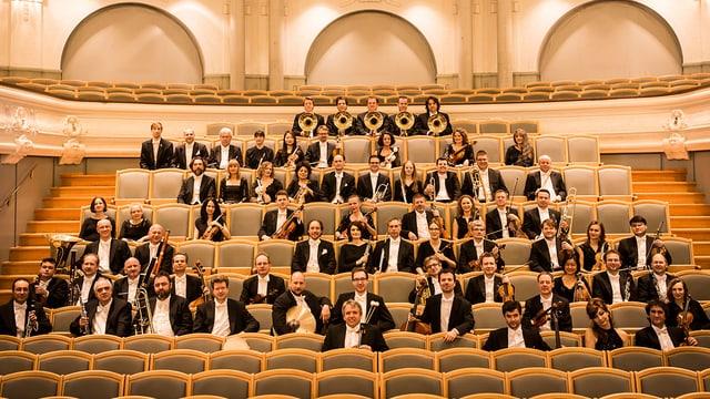 Mitglieder des Orchesters sitzen in den Zuschauerrängen.