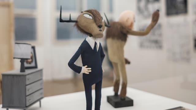Zwei Trickfilm-Puppen und Möbelstücke in einer Vitrine