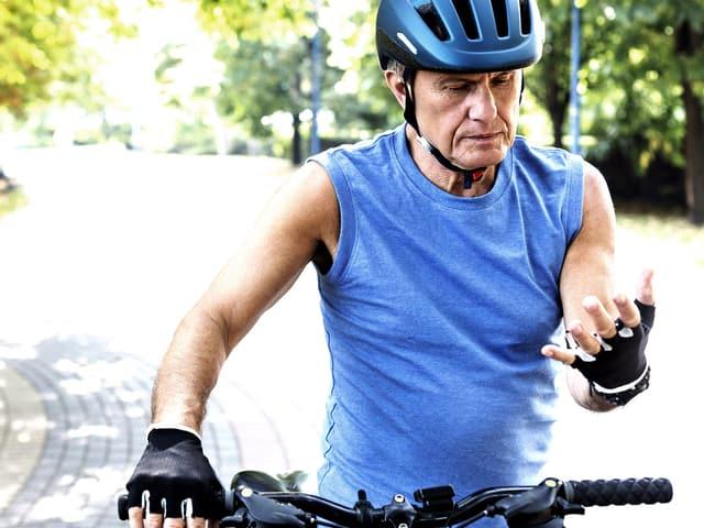 Älterer Veliofahrer betrachtet sinnend seine Hand.