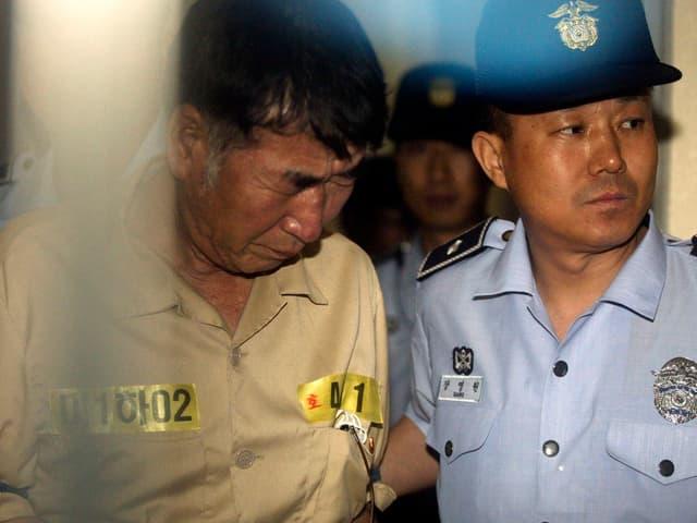 Der Kapitän der «Sewol» wird von einem Polizisten in den Gerichtssaal geführt.