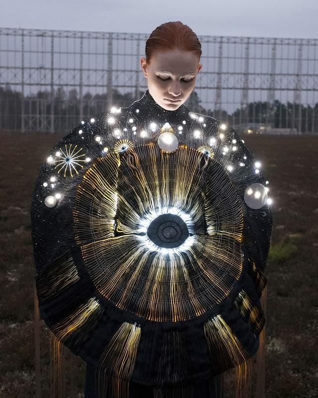 Ein Frau steht auf einer Wiese in einem schwarzen Kleid, mit zahlreichen leuchtenden Elementen