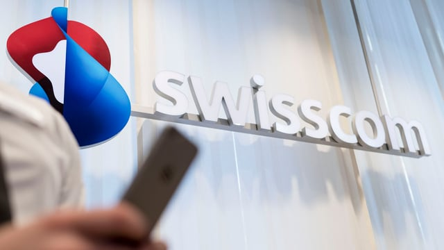 Swisscom-Logo. Im Vordergrund eine Person mit einem Handy.
