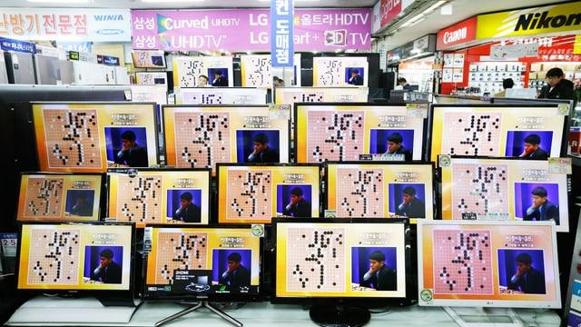 Bildschirme, die das Spiel zwischen dem Computer und dem Menschen zeigen.
