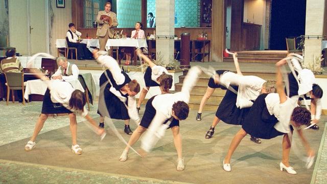 Blick auf eine Theaterbühne mit vielen Tänzerinnen im schwarz-weissen Gewand im Vordergrund
