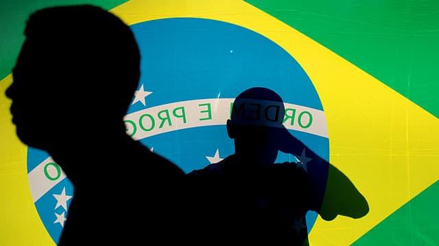 Brasilien-Fahne, darauf sind die Umrisse von Menschen zu erkennen.