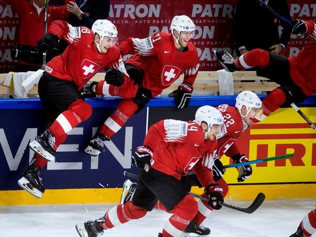 Vier Schweizer Spieler springen über die Bande.