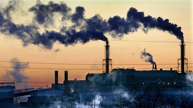 Fabrikkamine mit schwarzem Rauch in der Abenddämmerung