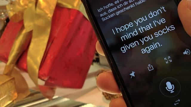 Ein Smartphone vor einem schön verpackten Geschenk