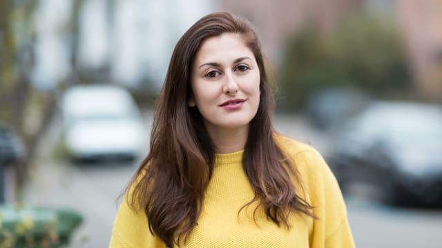 Porträt einer jungen Frau mit gelbem Pulli und Nasenpiercing.
