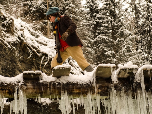 Schellenursli läuft über die Holzbrücke, an der Eiszapfen hängen.