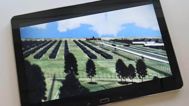 Tablet, auf dem eine Computergrafik von Auschwitz zu sehen ist.