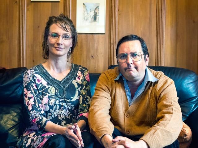 Eine Frau und ein Mann sitzen auf einem schwarzen Sofa vor einer braunen Holzwand.