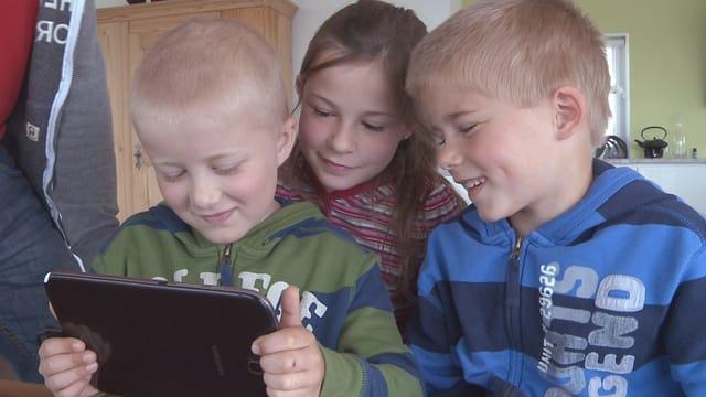Drei Kinder sitzen vor einem Tablet.