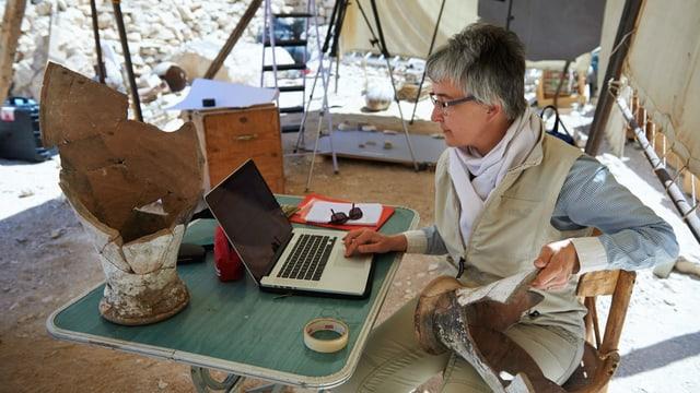Susanne Bickel arbeitet am Computer. Sie ist an einem Ausgrabungsort.