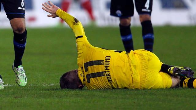 Marco Reus wälzt sich nach dem rüden Foul von Paderborns Marvin Bakalorz verletzt am Boden.