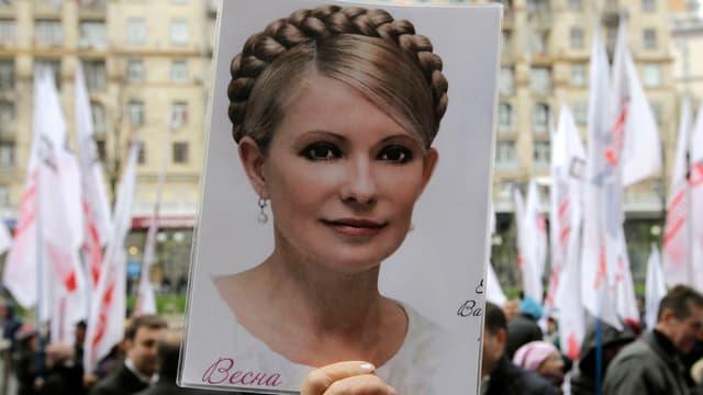 Demonstrant in Kiew mit einem Porträt Timoschenkos