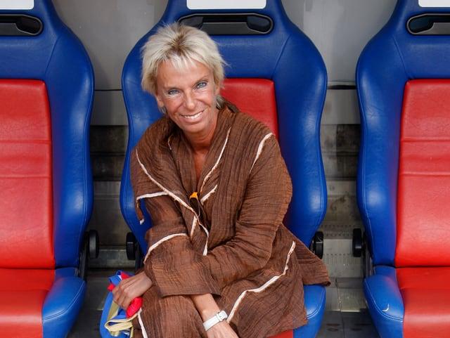 Frau sitzt auf rotblauem Stuhl. Sie ist sehr braun und blondiert.