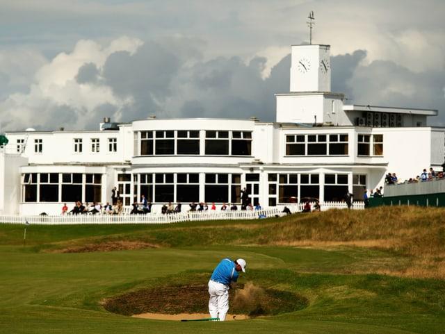 Ein Golfer steht vor dem Klubhaus im Bunker und schlägt den Ball.