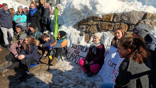 Schülerinnen und Schüler sitzen in Davos neben Greta Thunberg am Boden.