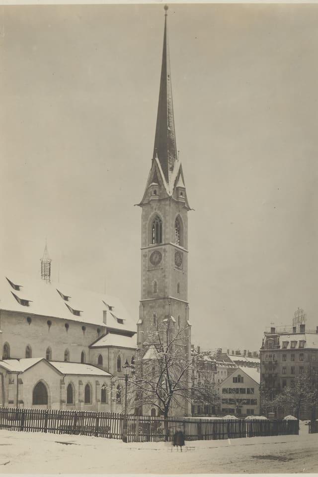 Ein Kirchturm steht in einer verschneiten Landschaft.