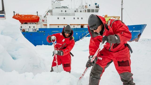 Teilnehmer der Expedition räumen einen Landeplatz für den Helikopter frei. Unmengen von Schnee umgeben sie, sie tragen rote Anzüge.