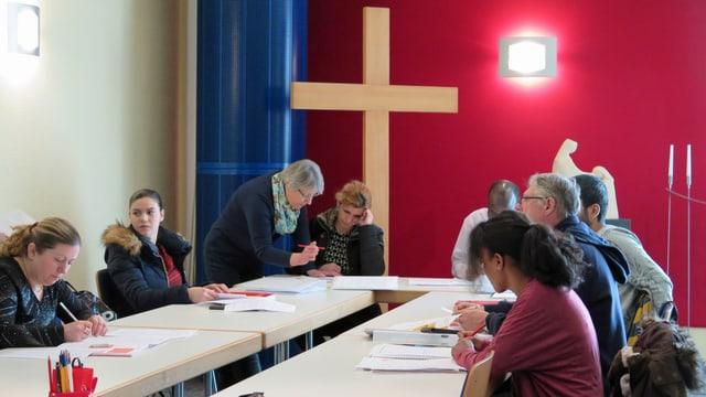 Ausländerinnen und Ausländer an einem Tisch, dahinter ein grosses Kreuz