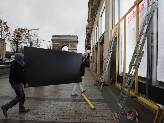 Zwei Männer montieren Holzplatten vor ein Schaufenster