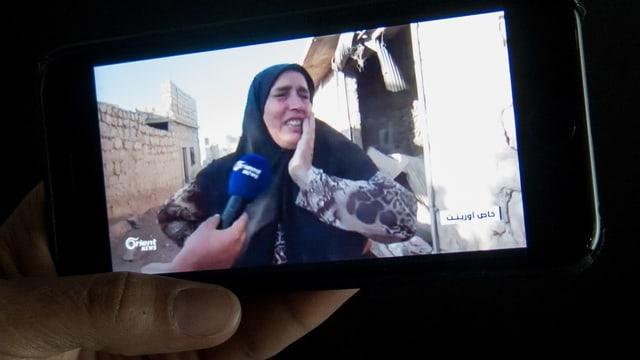 Eine weinende Frau hält die Hand an die Wange und spricht in ein Mikrofon.