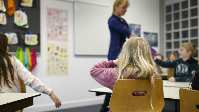 Symbolbild: Kinder und Lehrerin in einem Schulzimmer.
