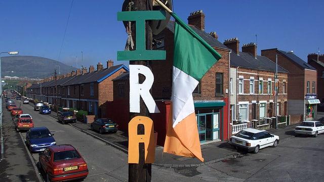 Blick in eine nordirische Strasse. Ein IRA-Logo hängt an einem Pfosten.