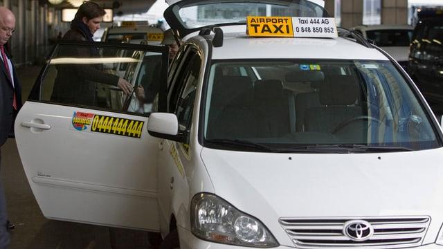 Taxi nimmt am Flughafen einen Fahrgast auf.