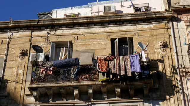 Altes Haus an dem die Wäsche am Balkon hängt.