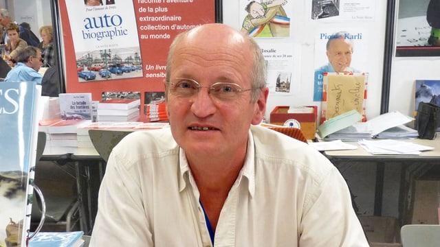 Ein Mann mit Glatze und Brille, im Hintergrund ein Tisch mit Büchern udn Broschüren..