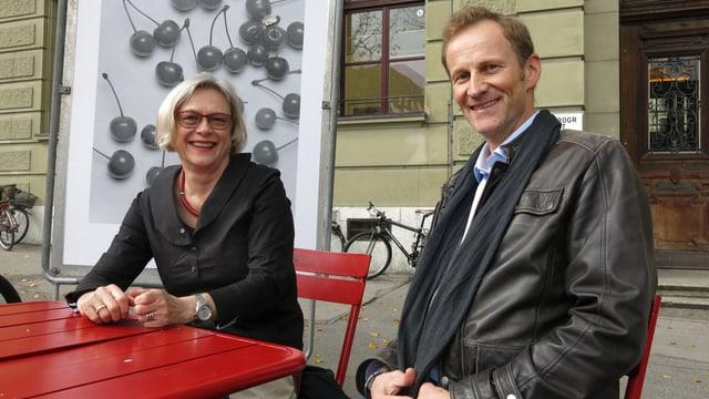 Zwei Personen an einem roten Tisch.
