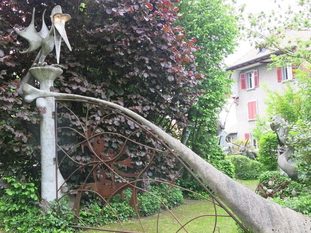 Ein Tor aus Beton, darauf ein Vogel mit leuchtenden Augen.